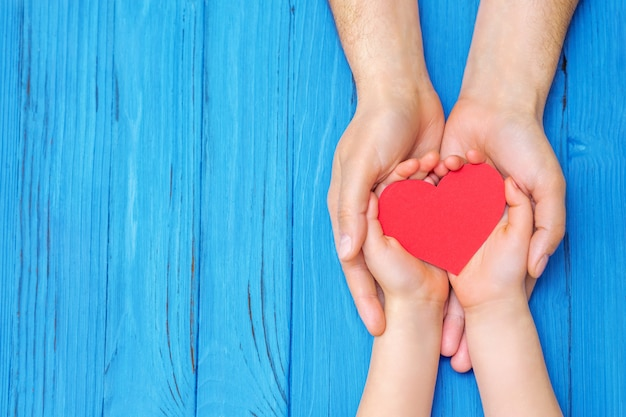 Child and dad hands holding red heart. Premium Photo