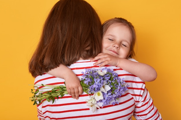 Child daughter congratulates mom and gives her flowers. mum and little girl hugging, charming kid closes eyes while enjoying moments.