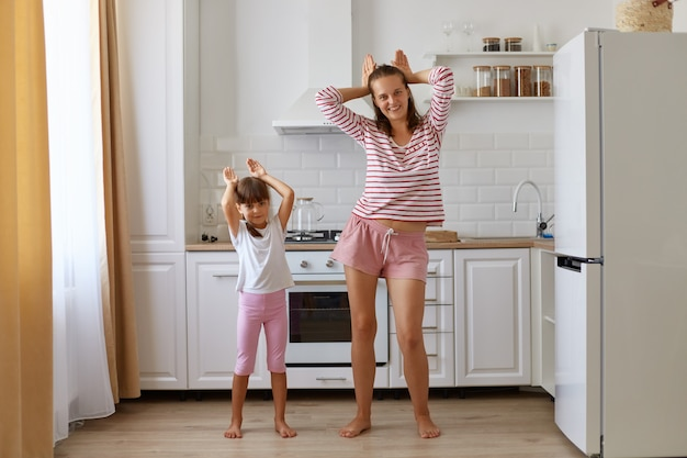 Child daughter and mom having fun in the kitchen at home, people wearing t shirts and shorts, dancing together, making bunny ears, looking at camera, have positive expressions.