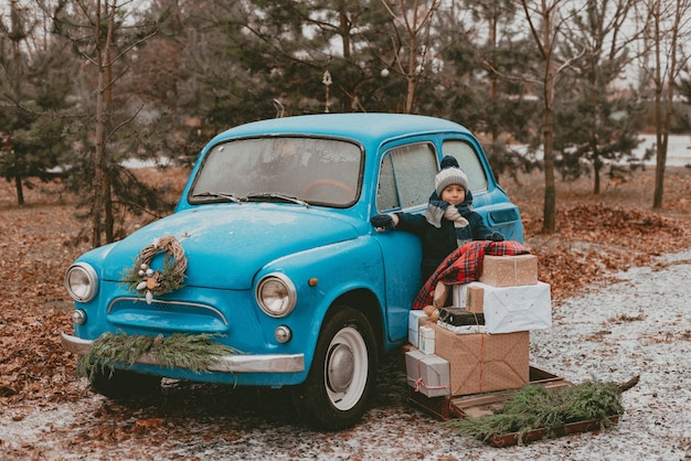 축제 크리스마스 트리 분기, 공예 포장지의 선물 상자, 소나무 전나무 바늘의 화환이있는 파란색 복고풍 자동차로 장식 된 어린이. 새해 가족 여행. 어린 시절의 꿈, 추억, 욕망.