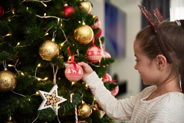 Bambino che decora l'albero di natale