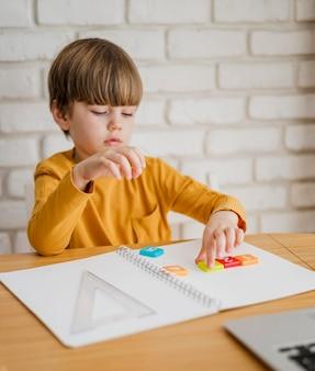 Il bambino alla scrivania è tutorato online