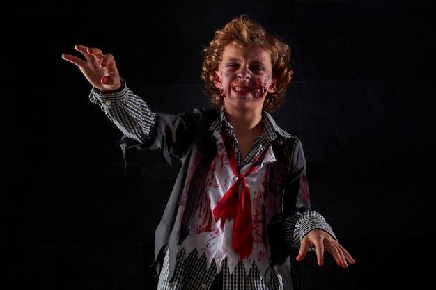 Ребенок, замаскированный под зомби с кровью и блеском, с поднятыми руками идет с выражением гнева