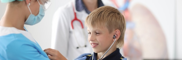Child at doctors appointment tries on stethoscope