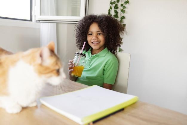 子供は家で宿題をし、猫を見ながらさわやかな飲み物を飲むために休憩します