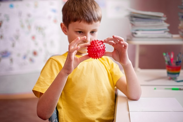 Child doing homework at home. child holds an a coronavirus red model