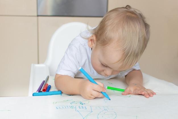 Ребенок рисует фломастерами, играет дома, малыш с развивающими игрушками для творчества