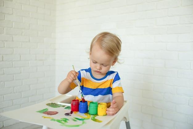 Ребенок рисует красками, играя дома. малыш с развивающими игрушками для творчества