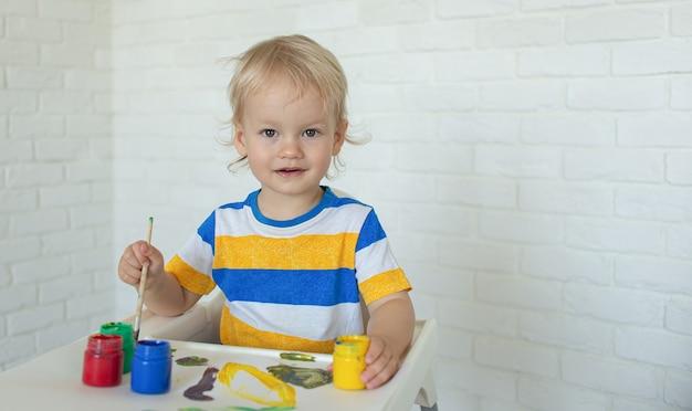 Ребенок рисует красками, улыбается, играя. малыш с развивающими игрушками для творчества. мальчик играет дома