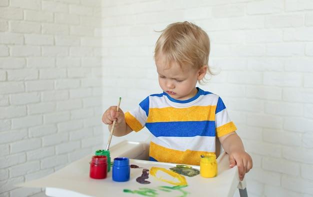 Ребенок рисует красками. малыш с развивающими игрушками для творчества. ребенок играет дома.