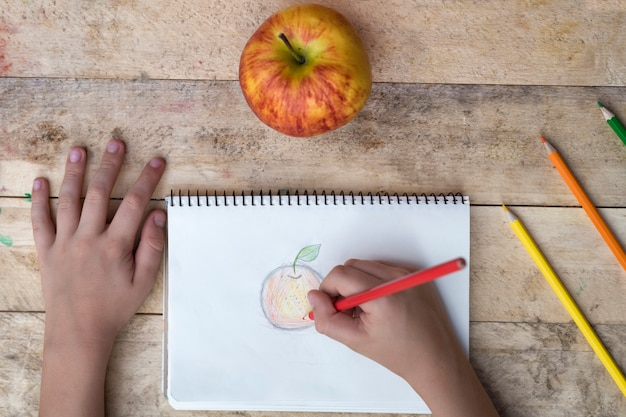 Child drawing an apple with colorful pencils