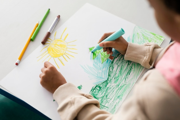Child drawing a beautiful landscape