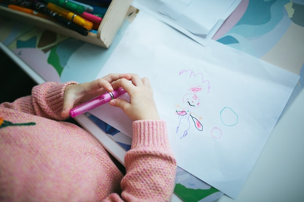 Child drawing happy fairy on paper. top view