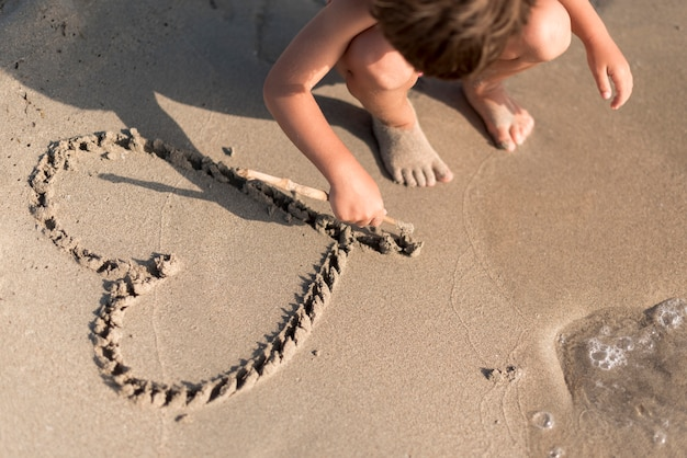 Child drawing a heart in the sand