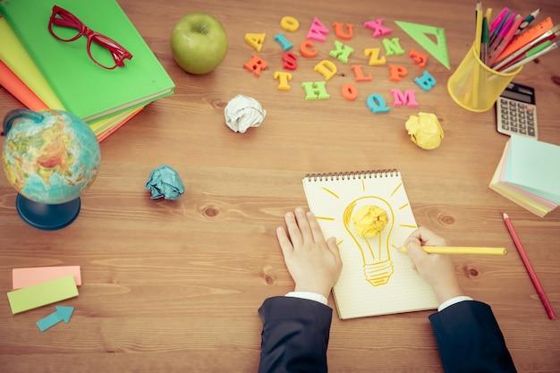 Детский рисунок лампа лампы в тетради школьные принадлежности на деревянном столе в классе новая концепция яркой идеи
