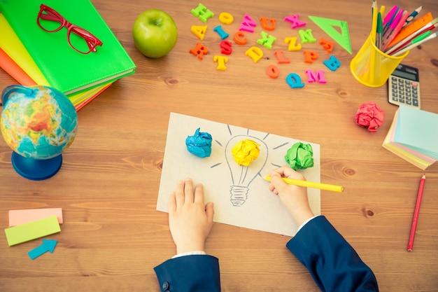 Ребенок рисует лампочку лампы на бумаге школьные принадлежности на деревянном столе в классе новая концепция яркой идеи