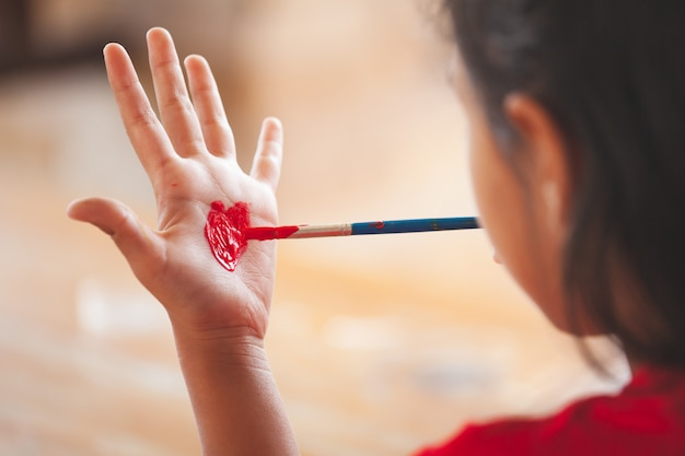 Child drawing and painting a heart on her hand with fun