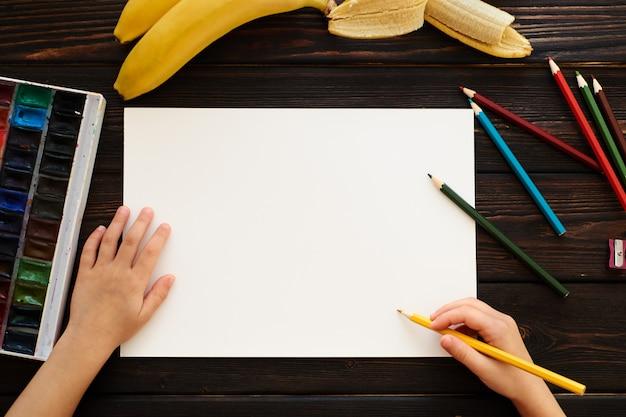 机に座って絵を描く子
