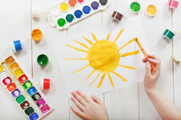 Child drawing yellow sun.