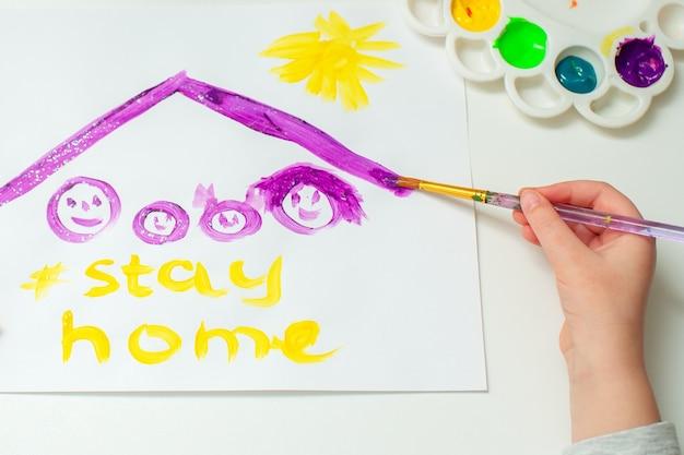 Ребенок рисует семью под крышей.