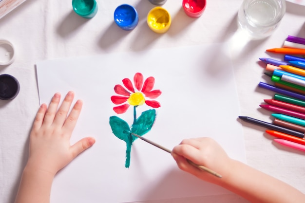 A child draws flower with colored paints on the paper.