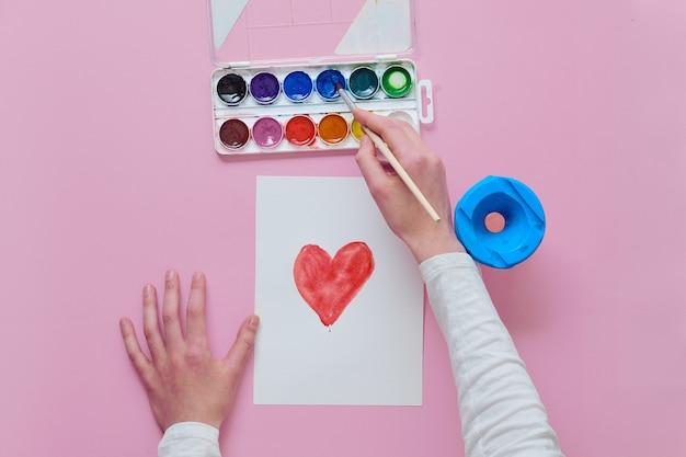 The child draws a heart, uses a brush and watercolor paints