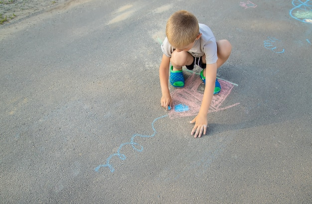 Child draws a house in chalk on the pavement. selective focus.