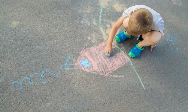 Child draws a house in chalk on the pavement