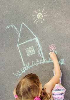 The child draws the house with chalk on the asphalt. selective focus.