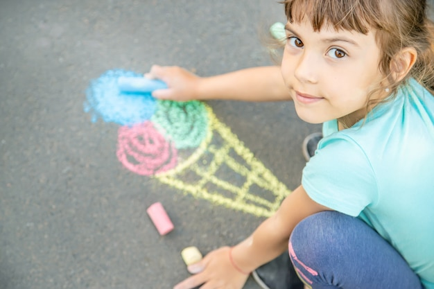 Child draws ice cream on asphalt with chalk. selective focus.