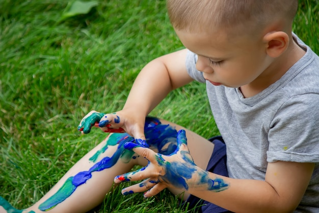 The child draws a pattern on the leg. a funny drawing with bright colors on the body. selective focus