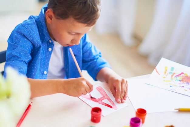 The child draws with a brush watercolor paints on paper the letter a