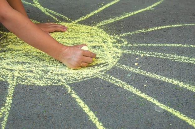 子供は歩道にチョークで描きます。セレクティブfocus.arts