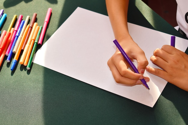 The child draws with felt-tip pens on paper. the development of children in kindergarten.