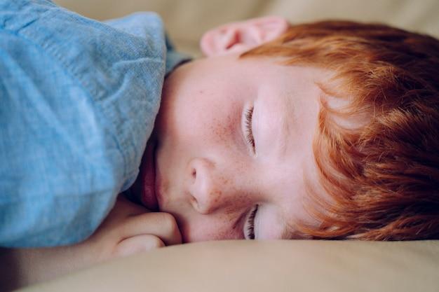 꿈꾸는 아이. 가족 관리 및 보육 개념. 그의 침실에서 낮잠 사랑스러운 빨간 머리 아들. 작은 아이가 침대에서 자 고