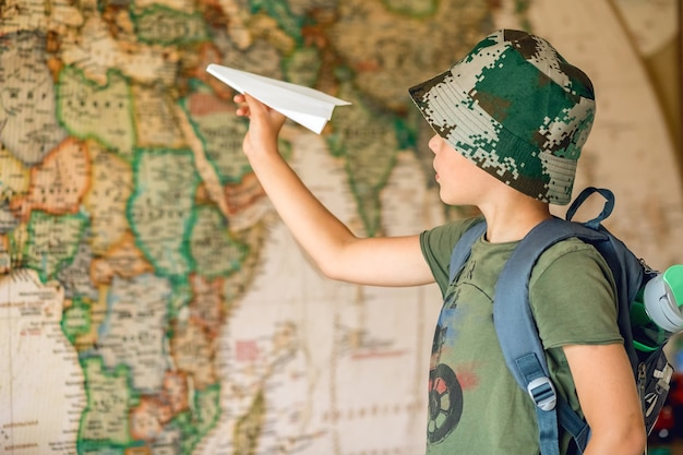 Child dreaming of travel plays with a handmade paper airplane