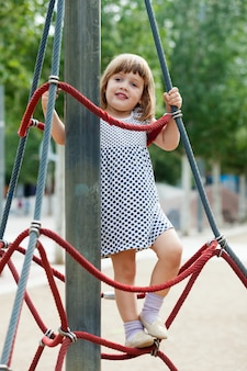 Child in dress climbing at ropes