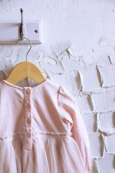 Child dress on hanger on white wall