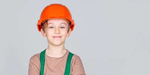 워커 빌더로 분장한 아이. 헬멧을 쓰고 어린 소년입니다. 안전모에 세로 작은 작성기. 어린이 건물 헬멧, 안전모. 헬멧에 작은 빌더