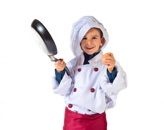 Child dressed as a chef holding fried pan