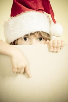 Ребенок, одетый в санта-клауса с концепцией рождественских праздников пустой бумаги