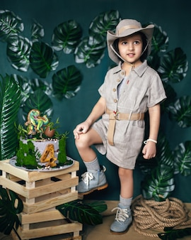 Child dressed in the style of a jungle treasure hunter with a hat and a dinosaur cake