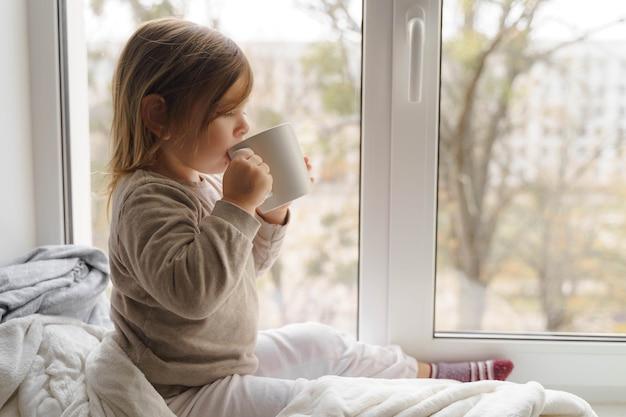 큰 흰색 머그잔에서 창 근처 어린이 음료 코코아 또는 우유