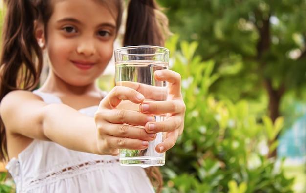 自然の中で純粋な水を飲む子供。selectivfokus.nature