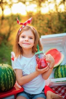 Ребенок пить арбуз лимонад в банку со льдом и мяты как летний освежающий напиток. холодные безалкогольные напитки с фруктами