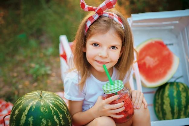 Ребенок пьет арбузный лимонад в банке со льдом и мятой как летний освежающий напиток