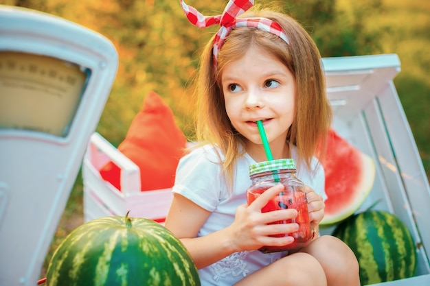 Child drinking watermelon lemonade in jar with ice and mint as summer refreshing drink. cold soft drinks with fruit