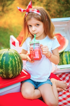 Child drinking watermelon lemonade in jar with ice and mint as summer refreshing drink