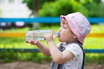 Child drinks from plastic bottle