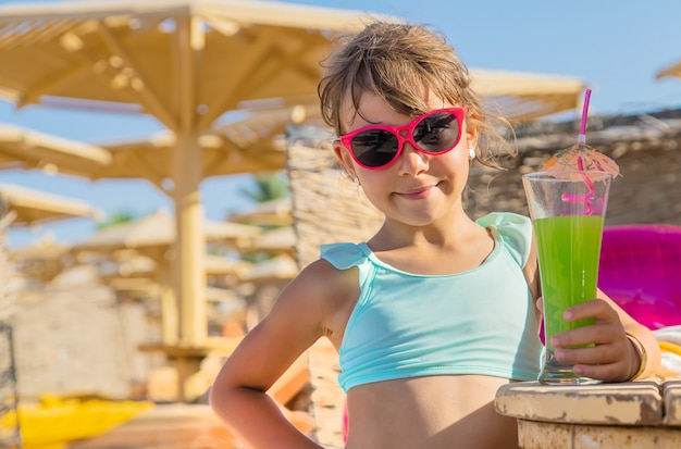 Child drinks a smoothie at the beach